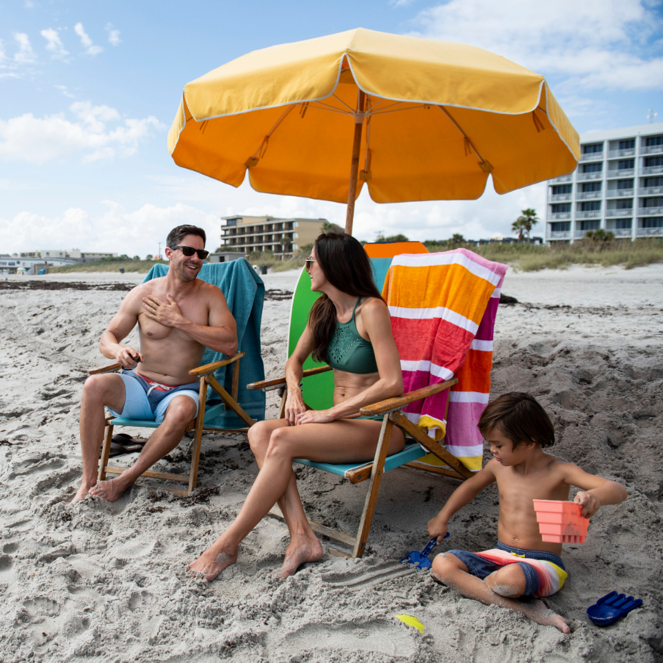 Family Playing On Beach under Umbrella